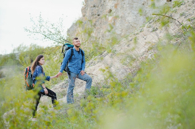 Hiker guy gives a hand to the girl while walking in the mountains