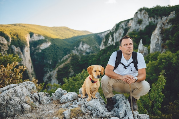 Hiker and his dog sitting on the mountain top