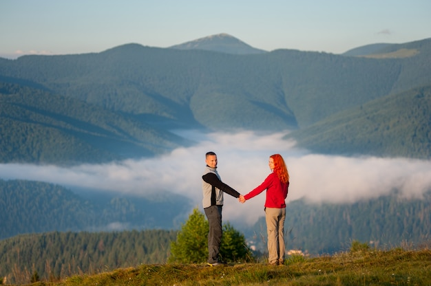 Hiker holding hands girl standing on a hill