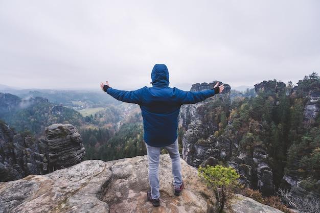アウトドアウェアを着たハイカーが山の頂上で手を上げ、崖の尾根の景色を楽しんでいます