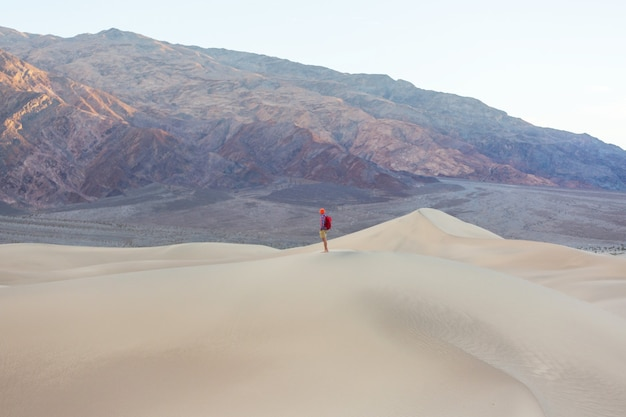 砂砂漠のハイカー。日の出時間。