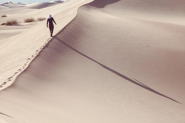 모래 사막에서 등산객. 일출 시간.
