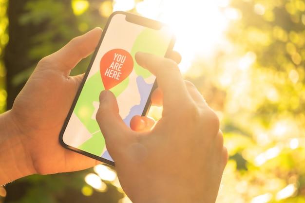 Путешественник использует мобильный телефон для навигации в лесу