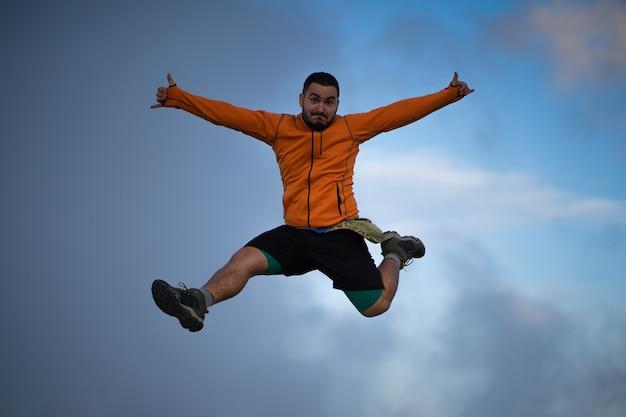 등산객이 점프하고 산 정상에서 멋진 일몰을 즐깁니다.
