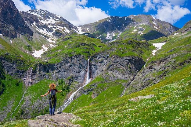 Hiker смотря водопад на горе