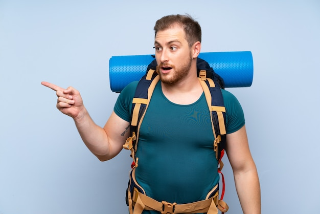Hiker man over blue wall surprised and pointing finger to the side