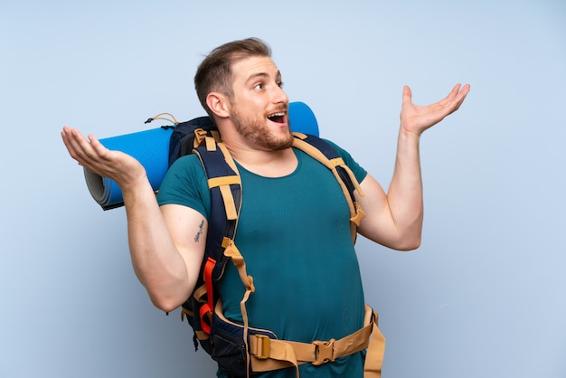 Hiker man over blue wall with surprise facial expression