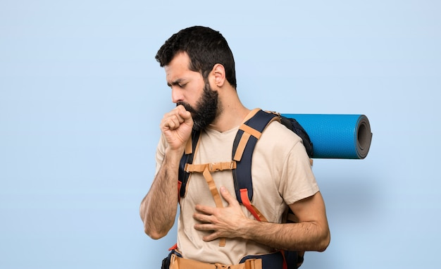 Hiker man is suffering with cough and feeling bad over isolated blue background