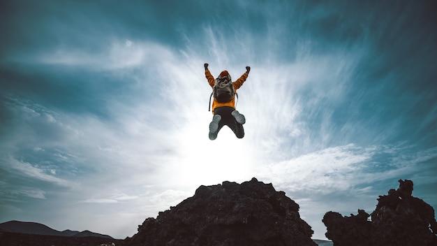 일몰에 산 위로 점프 등산객 남자. 자유, 위험, 성공 및 도전