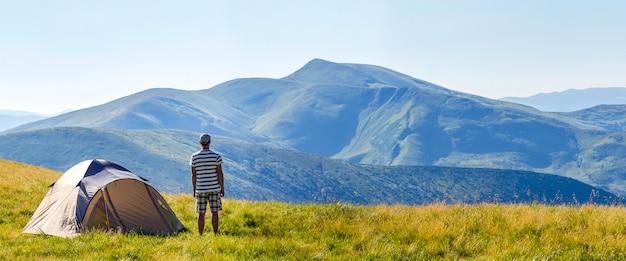 Человек путешественника стоя около располагаясь лагерем шатра в прикарпатских горах.
