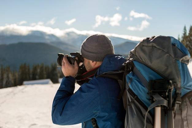 晴れた冬の寒い日に青い空の下で雪の谷と木質の山頂の風景の写真を撮るバックパックとカメラと暖かい服を着たハイカーマンの観光写真家。