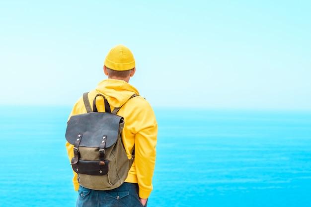 노란 옷을 입은 배낭을 메고 있는 등산객은 아름다운 바다를 바라보고 있습니다. 여름 여행 개념