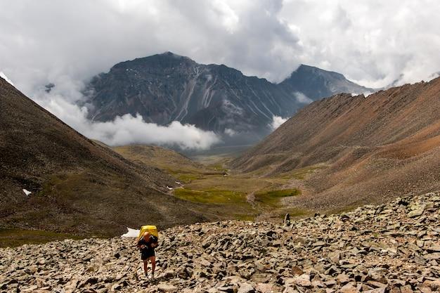 Путешественник с рюкзаком на камнях поднимается в гору. высокие горы и низкие белые облака. зеленая долина между горами. по горизонтали.