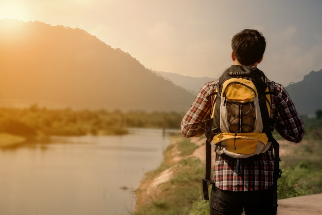 Hiker man with backpack and sleeping bag walking in the mountains in summer at sunset