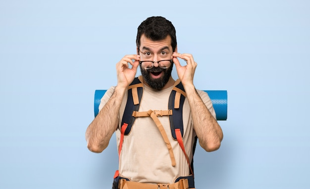 Hiker man with glasses and surprised over isolated blue background