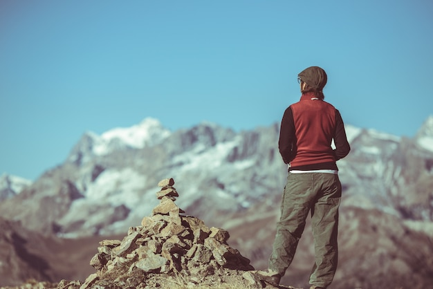 Hiker on mountain top looking at panoramic view, massif des ecrins national park, the alps
