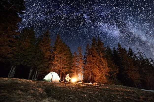 Hiker near campfire and tourist tent at night