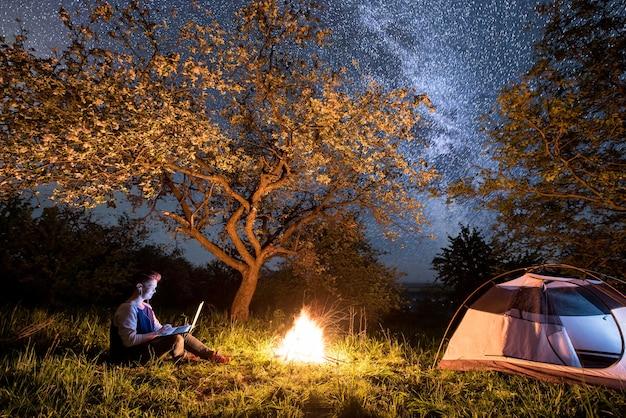 Hiker near campfire and tourist tent at night Premium Photo