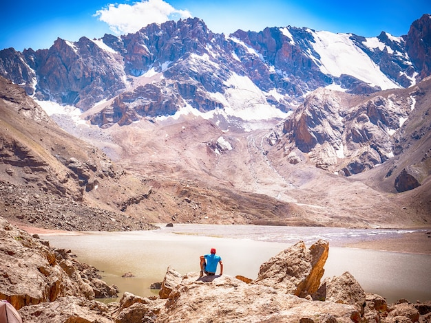 Hiker near lake moutniy on rocky mountain background