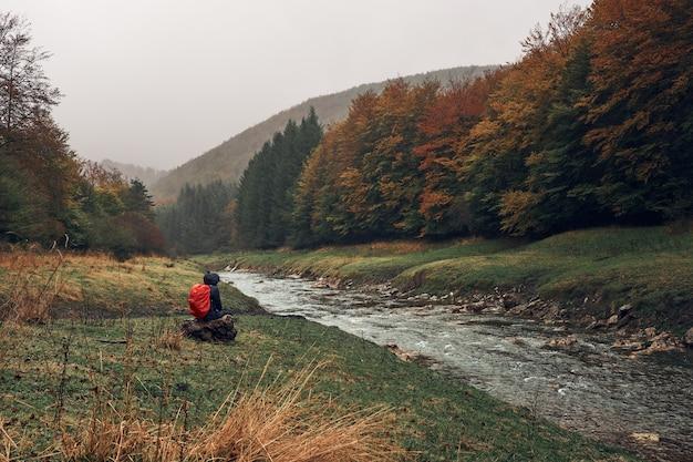 秋の森を囲む川の横にあるハイカー