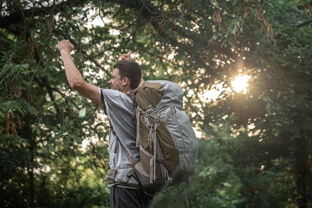 Путешественник в походе с большим рюкзаком на размытом фоне леса.