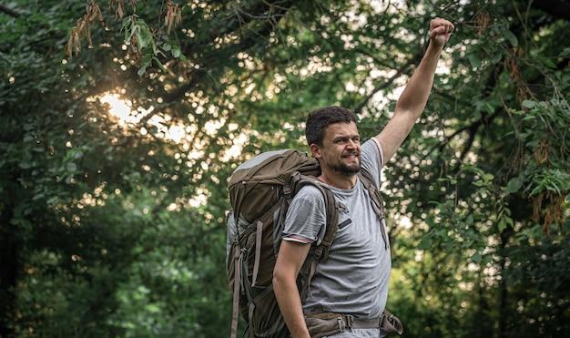 森のぼやけた背景に大きなバックパックを持ってハイキングをしているハイカー。