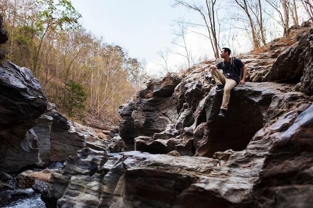 川の近くの岩の上の登山者