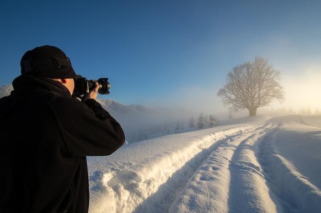 겨울 산에서 눈 덮인 자연의 사진을 찍는 등산객 사진 작가.