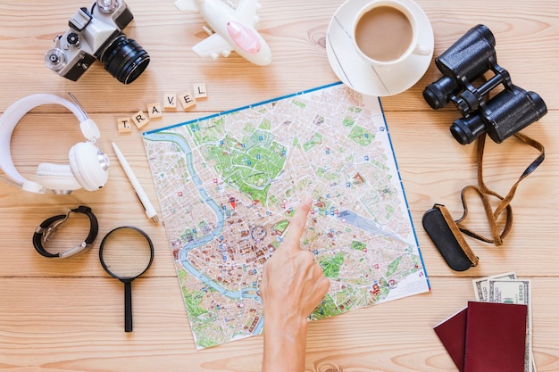 Hiker pointing at location on map with cup of tea and traveler accessories on wooden background