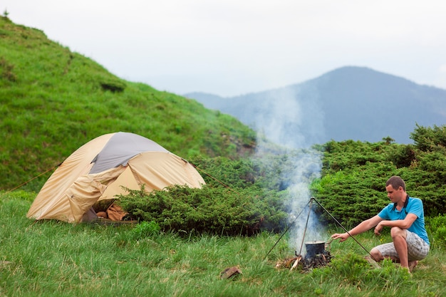 Hiker preparing food in a bowler on camping fire in mountains near tent