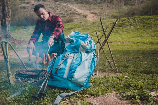 Hiker preparing sausages at campfire
