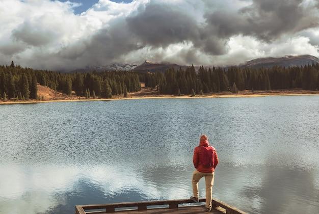 穏やかな山の湖でリラックスしたハイカー