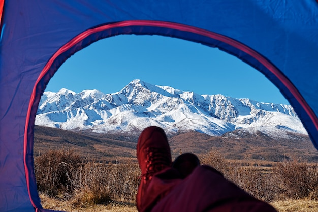 Hiker relaxing enjoying view from tent camping entrance outdoor. travel lifestyle concept adventure vacations outdoor.