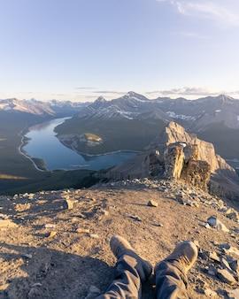 日没のリムウォールサミットカナダを待っている山の頂上で休んでいるハイカー