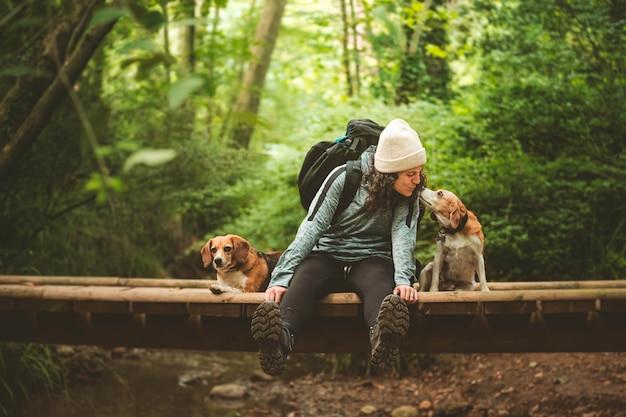 Путешественник отдыхает со своими собаками и целует одну из них.