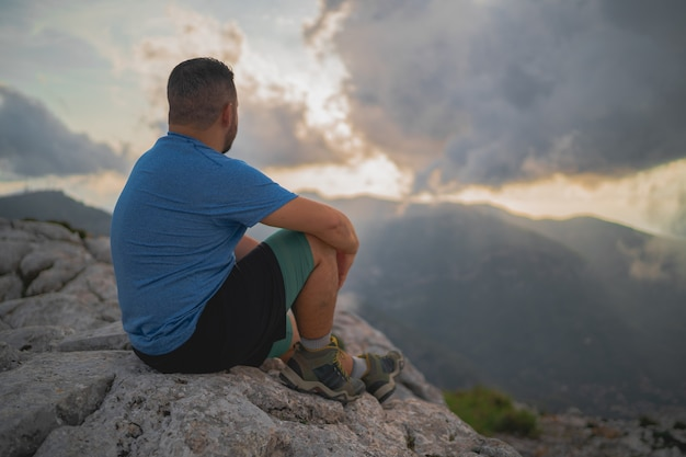 등산객은 일몰의 놀라운 전망을 고려하면서 바위에 앉아