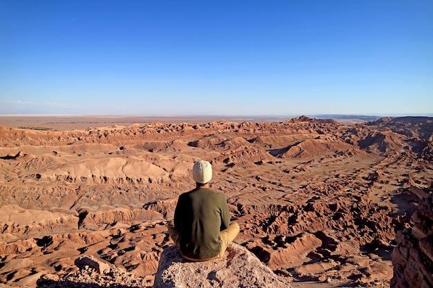 Путешественник сидит на скалистом утесе, любуясь пейзажем лунной долины в пустыне атакама, чили