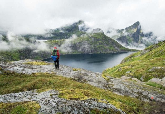 霧の日にロフォーテン山の湖の横に立っているハイカー