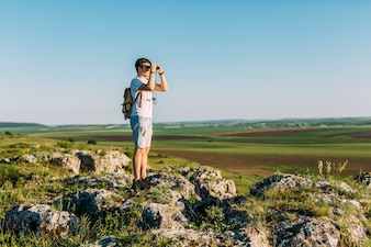 Hiker standing on rock looking through binocular