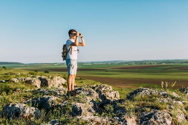 Hiker, стоящий на скале, смотрящий в бинокль