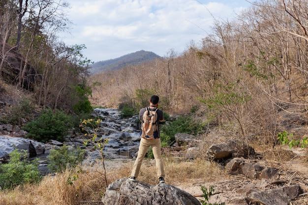 Escursionista in piedi sulla pietra davanti fiume