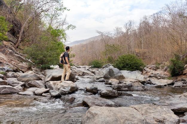 Escursionista sulla pietra in fiume selvaggio
