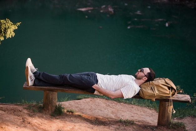 Hiker stylish man lying on a wooden bench near lake