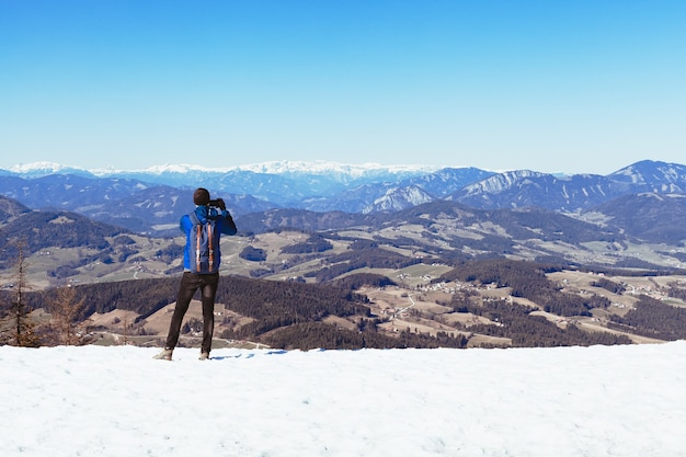 Hiker on the top of the mountain takes pictures on his smartphone