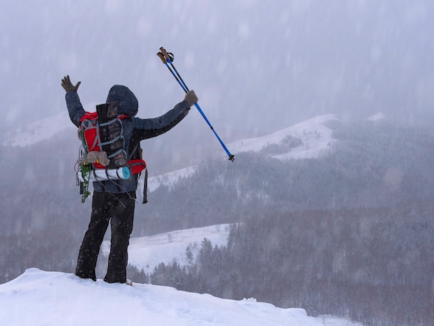 Hiker on the top of the mountain with his hands up. victory. tourism concept.