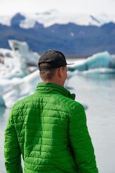 Путешественник турист смотрит на пейзаж айсберга с гигантскими айсбергами и озером