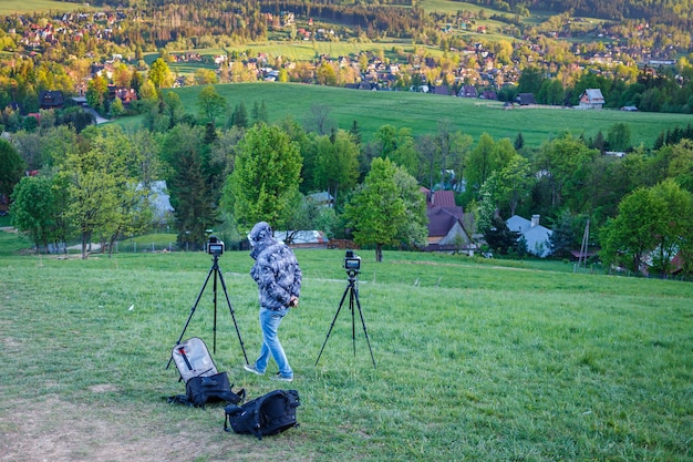 Hiker tourist professional photography shooting on tripod in mountains