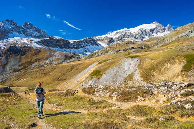 Hiker walking on a colorful valley with great panoramic view and vivid colors