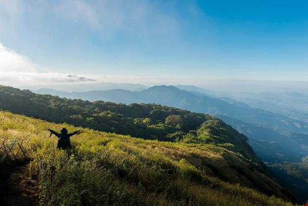 山の上を歩くハイカー。成功、自由、旅行、冒険のコンセプト
