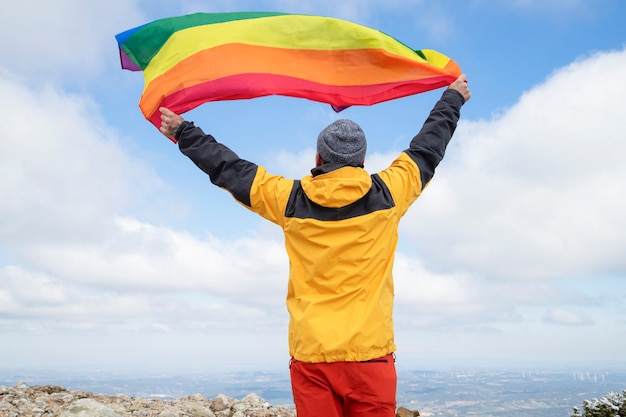 Hiker waving a rainbow lgbt pride flag in high mountains